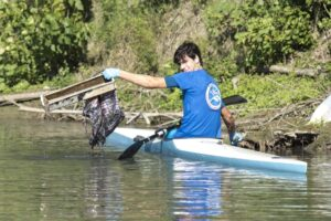 Attività in canoa volta a rimuovere i rifiuti in acqua